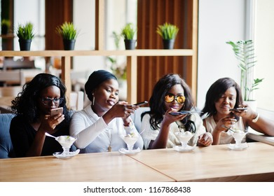 Four african american girls sitting on table at cafe with ice cream dessert and making food photo on phone.
