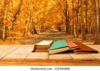 four aged book stack on wooden platform beside fresh autumn garden image for back to school concept.