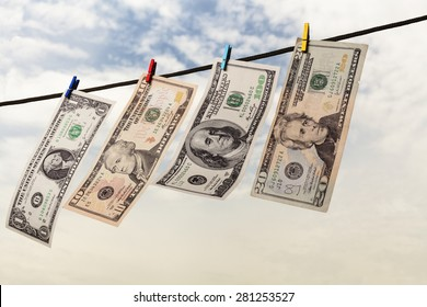 Four american dollars drying on string with sky and trees in the background