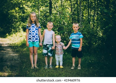 Four amicable children: One girl and three boys holding hands