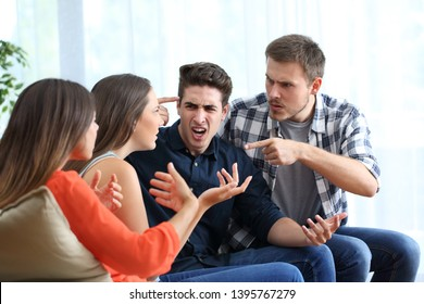 Four angry friends arguing accusing each others at home