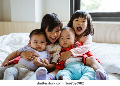 four Asian children laugh while sitting on the bed hugging each other