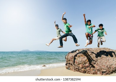 four asian male teenager jumping and having fun at the beach. concept of togetherness and friendship