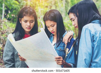 Four asian teenage looking at map while hiking in the forest. travel concept