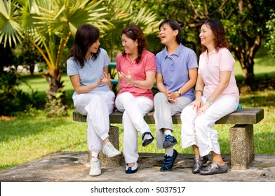 Four Asian women sitting on a bench in a park and talking