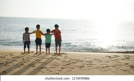 Four asian young brothers hugging each others watching the sunset. Brotherhood friendship concept