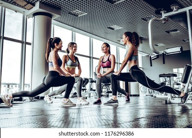 Four athletic woman performing low fallouts in gym with panoramic windows. Doing fitness exercises.