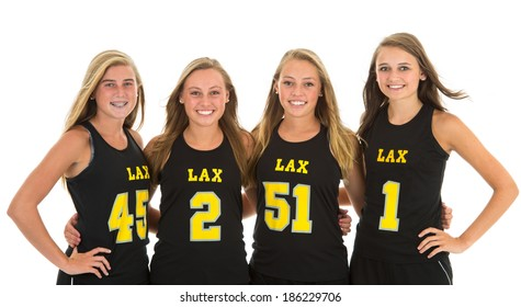 Four attractive members of a women's Lacrosse team. Studio shot, isolated on white background.