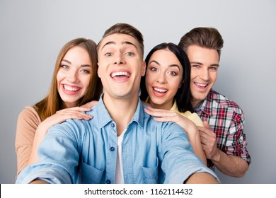 Four attractive nice young funky smiling friends, two girls and two guys wearing casual taking self picture. Isolated over grey background