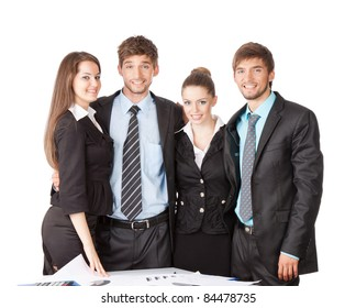 four attractive positive smile young business people in elegant suits standing at the desk with papers, Isolated over white background