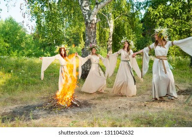 Four attractive Women with Wreath of Flowers dancing around bonfire. Ivan Kupala Holiday Celebration. Russia