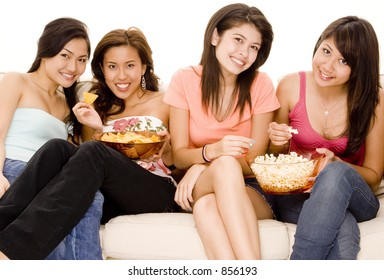 Four attractive young women sitting on a sofa with popcorn and corn chips