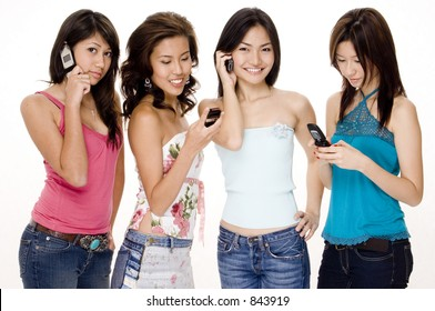Four attractive young women using their phones (cellphones/mobiles)