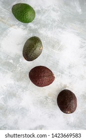 Four avocados in stages of ripening on rustic wooden background in flat lay composition.  Vertical format with room for text. Healthy eating concept.