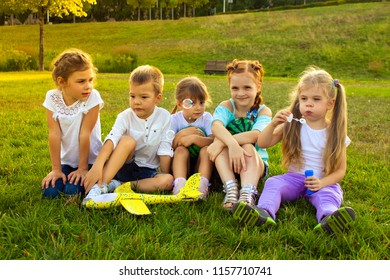 four babies are sitting with toys on a green glade