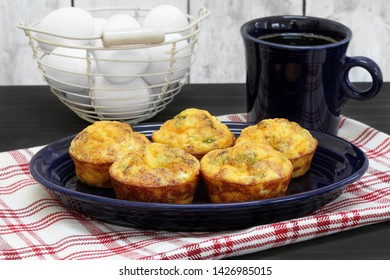 Four bacon, egg and cheese breakfast muffins on an oval platter.  Set in a breakfast setting with coffee and a basket of eggs.