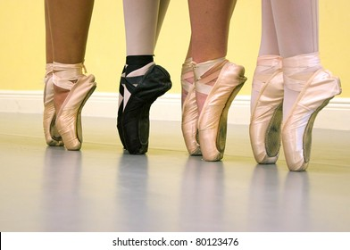 Four ballerinas are standing on their toes, on pointe, wearing ballet shoes of various types during dance class.