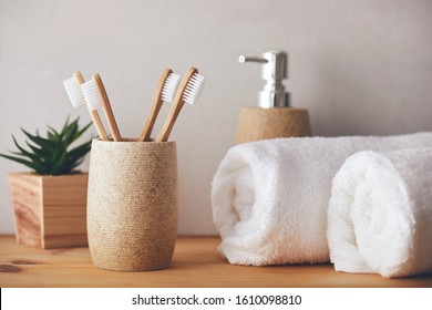 Four bamboo toothbrushes in a cup and white towels