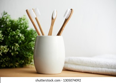 Four bamboo toothbrushes in a glass with copy space on a wooden background