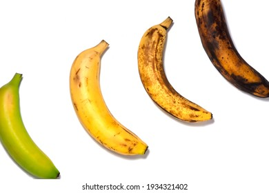 Four bananas - green underripe, ripe, very ripe and over ripe - in diagonal. Banana ripeness. Concept of life cycle, ranging from young to old. White background, isolated. - Shutterstock ID 1934321402