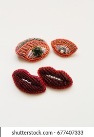 Four beaded unique brooches in shape of eyes and lips on white background.