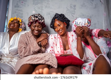 Four beautiful African girlfriends wearing hair bonnet and robes,laughing and having fun on vacation holidays,treatment at spa - Black Pretty bridesmaids indoors looking cheerful