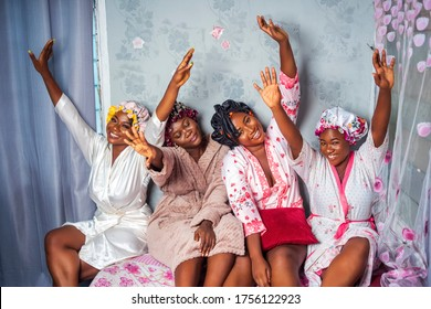 Four beautiful African women wearing robes and satin bonnet caps, laughing and having fun with hands raised up - Black millennial bridesmaids sitting, laughing - people enjoying on vacation travel