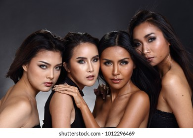 Four Beautiful Asian black hair tan skin women open shoulders, fashion make up, studio lighting black dark background, Group Models express fest and fashion inner feeling