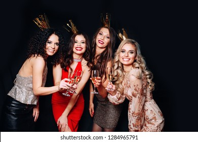 Four beautiful elegant women celebrate hen-party and drinking cocktails. Best friends wearing stylish evening dress, high heel shoes ,crown on head .Bright make up, red lips.