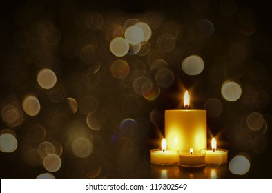 Four beautiful gold candles with sparkly gold bokeh lights
