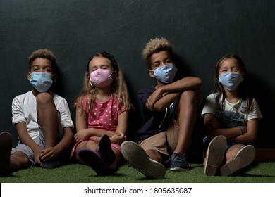 Four beautiful multinational children wears surgical protective cloth facemasks school age girls boys look at camera posing sitting leaned at dark grey wall background. Corona virus and kids concept