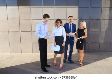 Four beautiful perspective people, two men and two women, young entrepreneurs, students, communicate, solve important problems, share of business ideas, make plans, hold in hands, consider and reading
