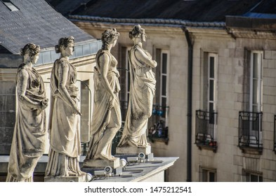 Four beautiful statues of women on the roof of the building of the Opera in Nantes, France. Close up. Sunny day