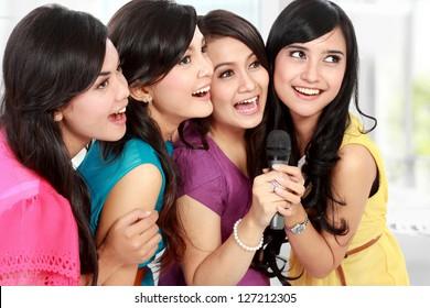 Four beautiful stylish woman singing karaoke together