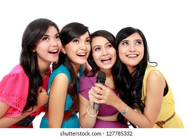 Four beautiful stylish woman singing karaoke together isolated over white background