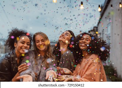 Four beautiful women standing at a terrace under confetti.