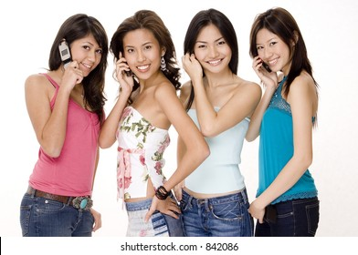 Four beautiful young asian women using their phones