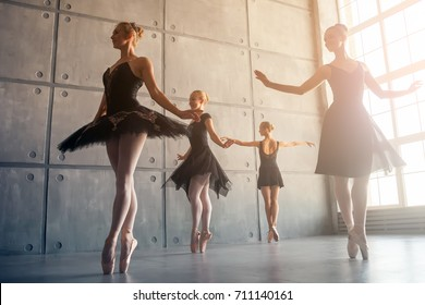 Four beautiful young Russian ballerinas in black packs, white pantyhose and ponts in the style of a black swan dance ballet in a black studio