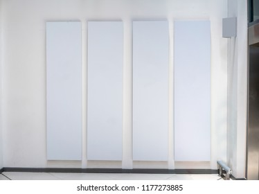 Four big vertical poster on white background in front of elevator