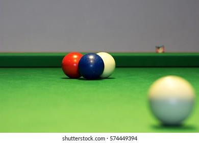 four billiards balls on a billiard table
