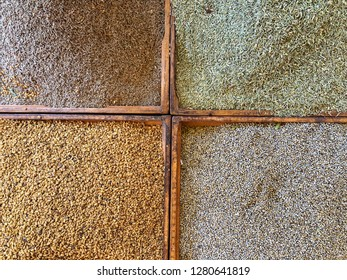 Four bins in a market stall are filled with different colored seeds or spices that make a nice background.