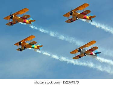 Four Biplanes Flying in Formation with Smoke