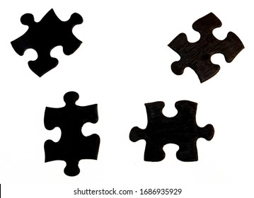 Four black hand-painted pieces of a jigsaw puzzle, irregularly spaced on white background. Keep separate or distance between each other, group potential concept.