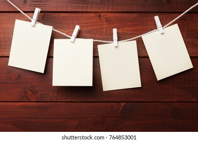 Four blank cardboard labels over brown wooden background.