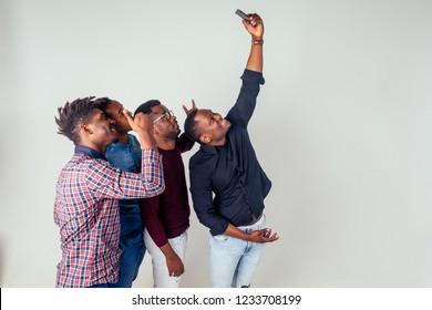 four blogger funny friends afro american men taking selfie in studio on white background