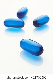 Four blue capsules on white background