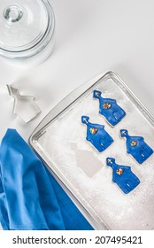 Four blue (church shaped) cookies on baking sheet with cutter, cookie jar, and blue napkin. Shot with copy space.