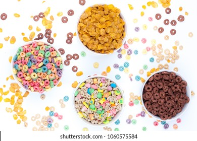 Four bowls of cereals and cereals scattered around the table on white background. A bowl of colored cereals, one of chocolate rings, one with cereals and marshmallow, and one with corn flex. Top view.