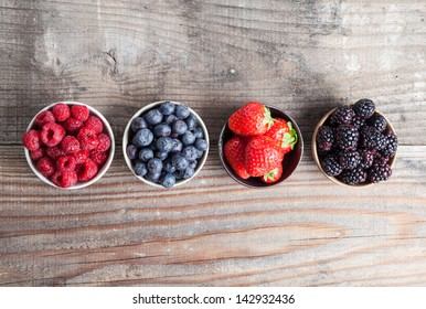 A four bowls overflowing with summer berries like strawberries, raspberries, blueberries and blackberries.