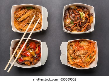 four boxes of Chinese food and chopsticks on dark background